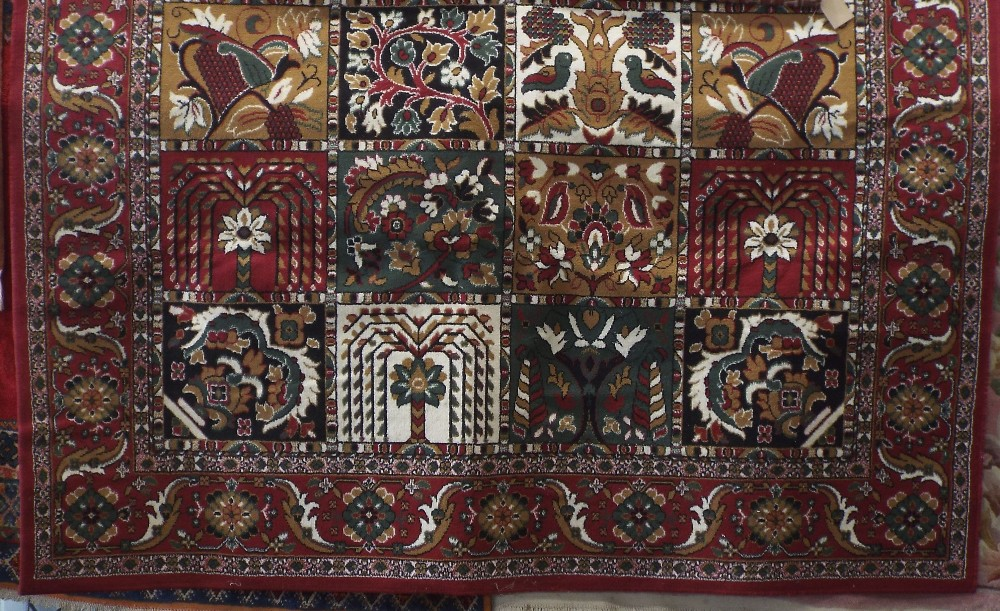 Lot 1437 - Belgian type rug decorated with various floral panels upon a red ground, 320 x 240 cm