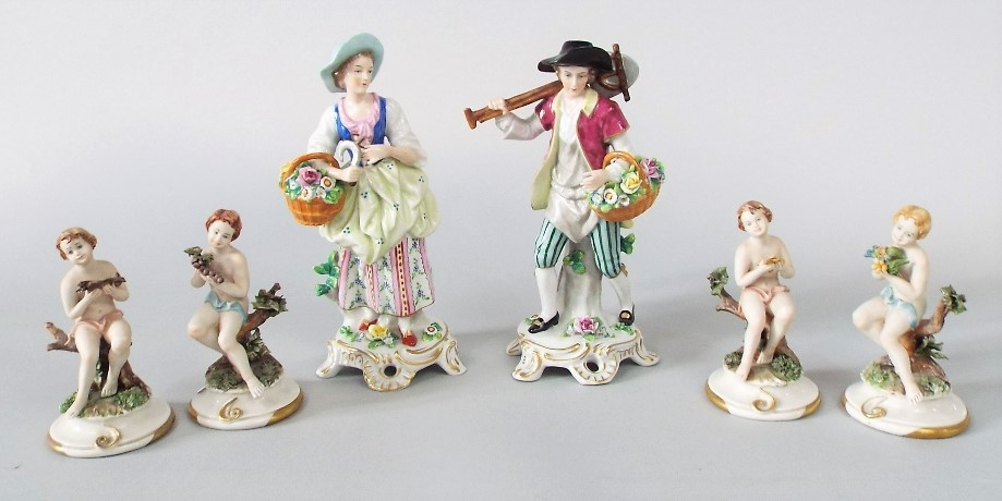 Lot 225 - A pair of continental figures of male and female gardeners with flower baskets, 24cm tall approx,