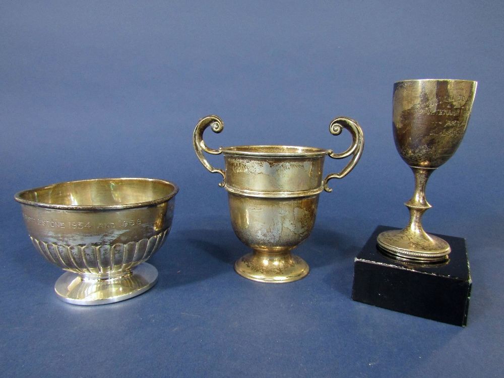 Lot 423 - Silver golfing twin handled trophy together with a further golfing pedestal bowl and further cup,