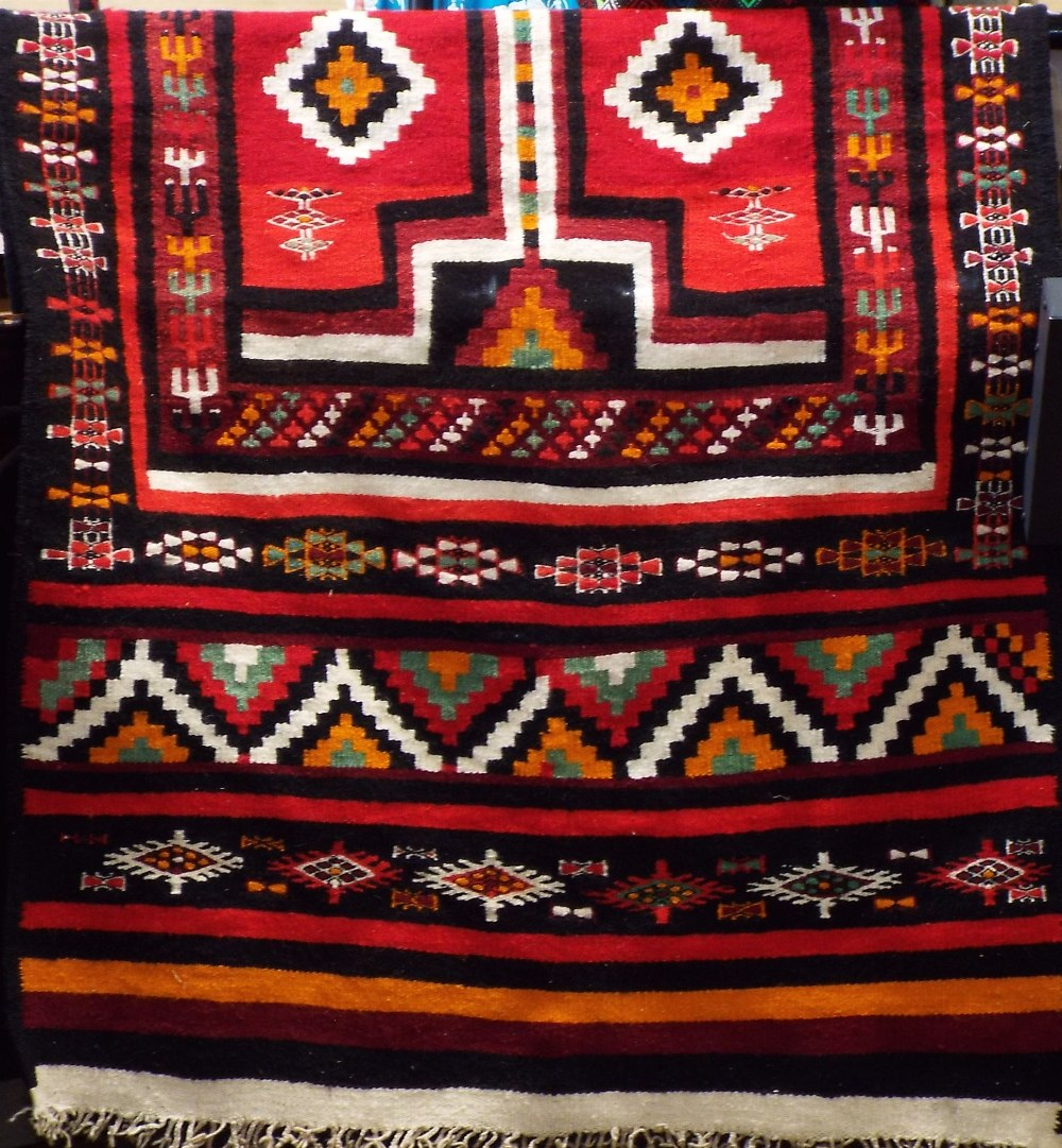 Lot 1422 - Full pile Kelim runner decorated with various red medallions upon a black ground, 240 x 125 cm