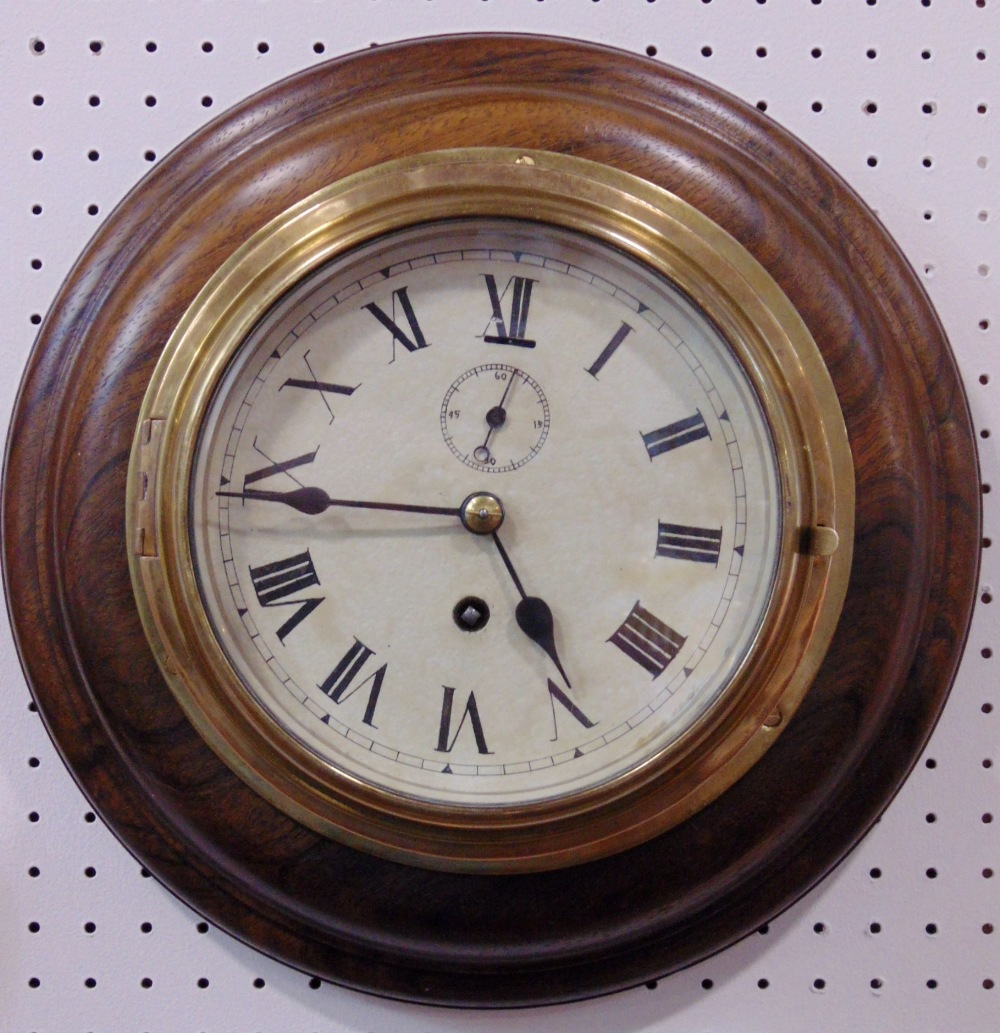 Lot 563 - A brass bulk head style wall clock, the 6 inch dial with Roman numerals and subsidiary second upon a
