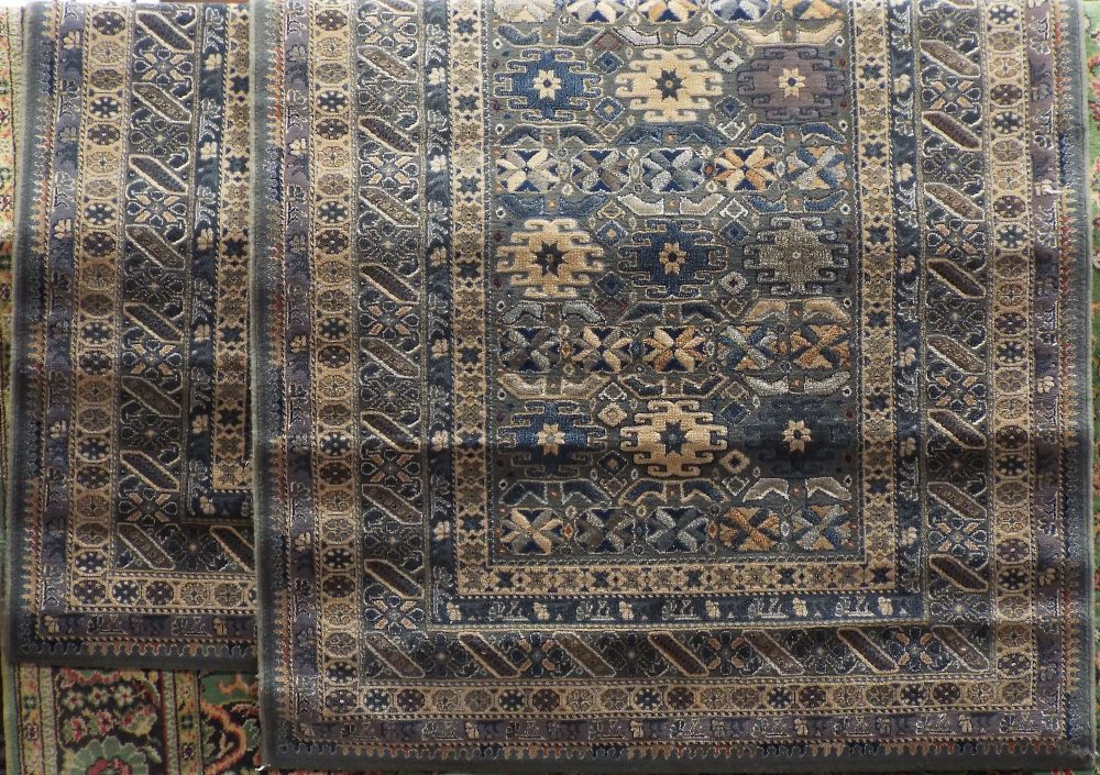 Lot 1438 - A pair of Belgian type kashan rugs with geometric decoration upon a blue ground, 210 x 130 cm (2)