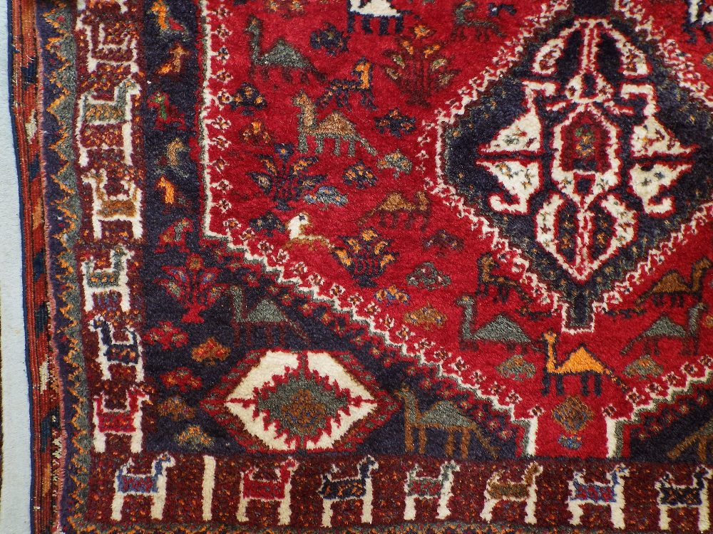 Lot 1428 - Afghan full pile rug decorated with three central medallions, framed by animal symbols and foliage