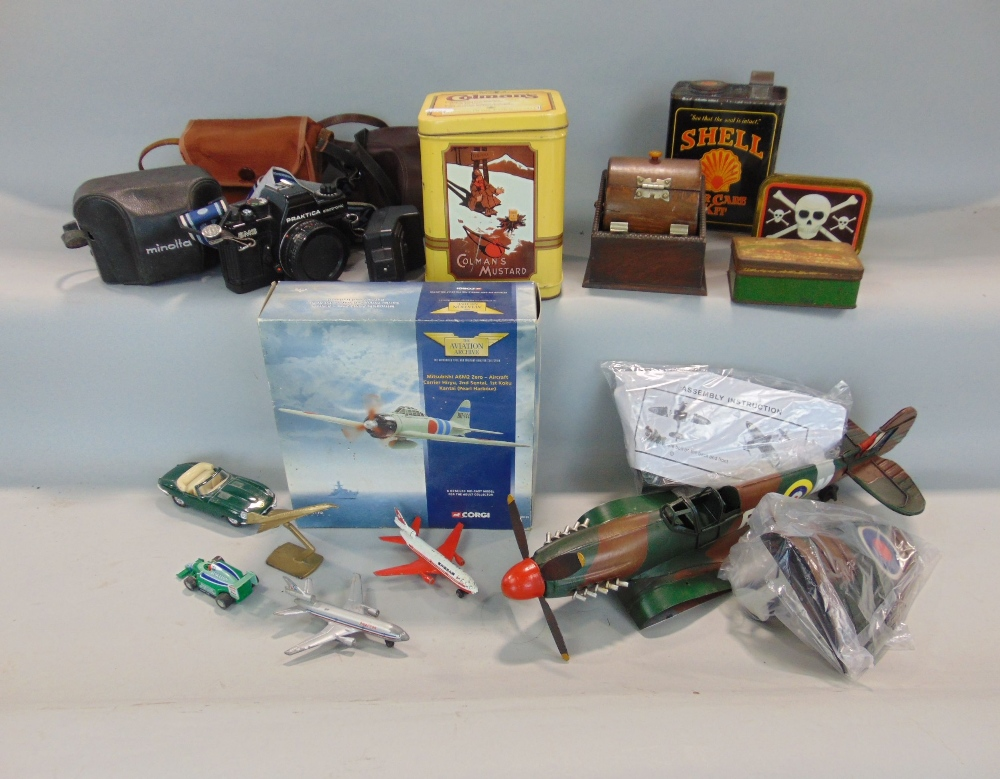 Lot 794 - A tin plate model of a Spitfire, with painted finish, never assembled, a timber cigarette dispenser,