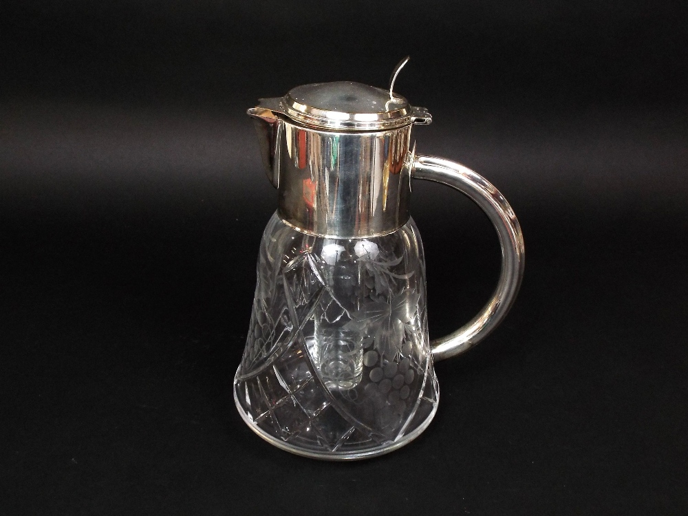 Lot 353 - A substantial glass jug with etched fruiting vine detail and inner cooling cavity, with plated mount