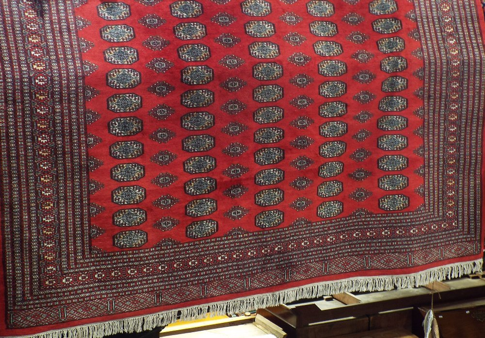 Lot 1431 - Good quality Bokhara carpet with typical geometric medallion decoration upon a red ground, 300 x 260
