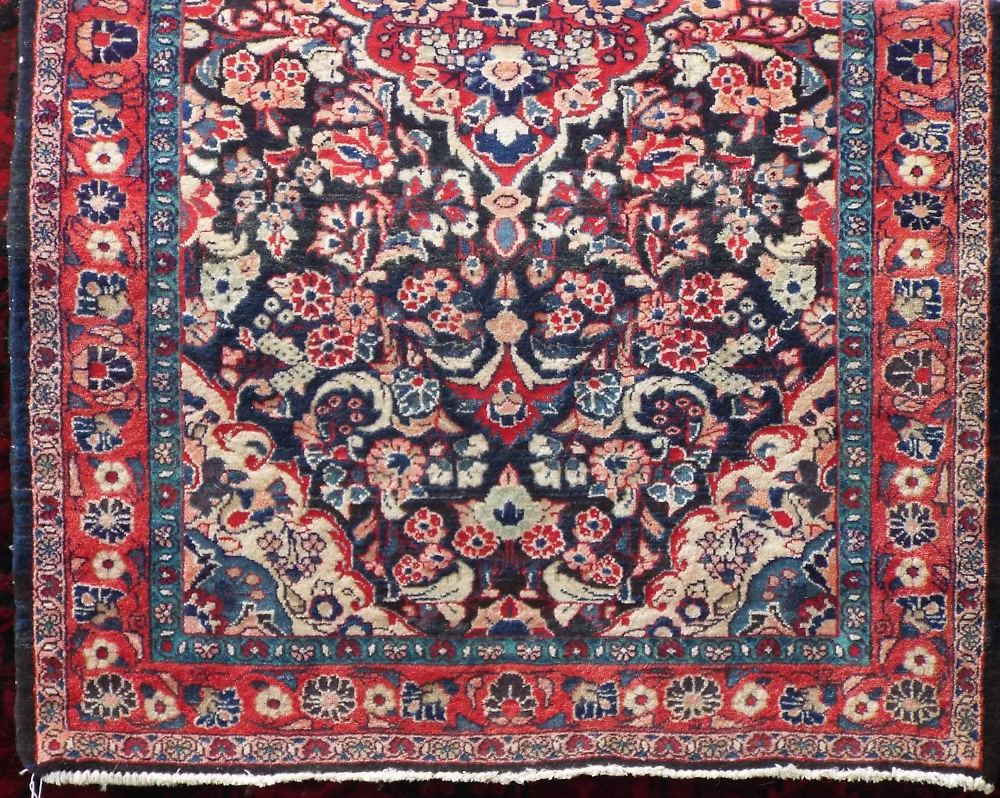 Lot 1412 - Persian full pile rug decorated with various floral sprays upon a navy blue ground, 210 x 130 cm