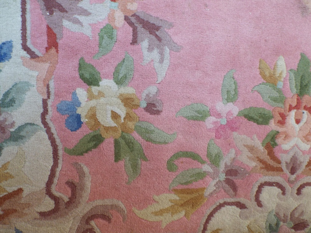 Lot 1413 - Chinese wool carpet with typical pastel shades upon a pink ground, 300 x 180 cm