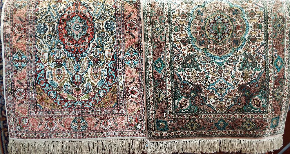 Lot 1444 - A pair of Persian silk prayer mats, one with a green colourway, the other with red, both on an ivory