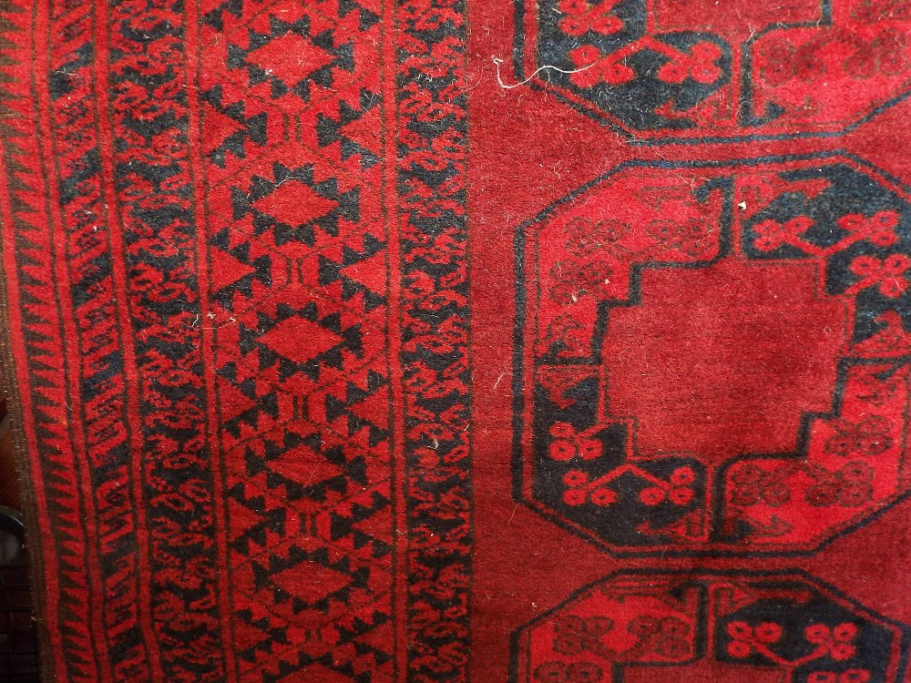 Lot 1411 - Bokhara carpet with typical large geometric medallions upon a deep red ground, 310 x 210 cm