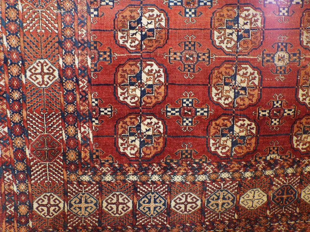 Lot 1426 - A Bokhara rug with typical coloured medallions upon a red ground, 260 x 180 cm