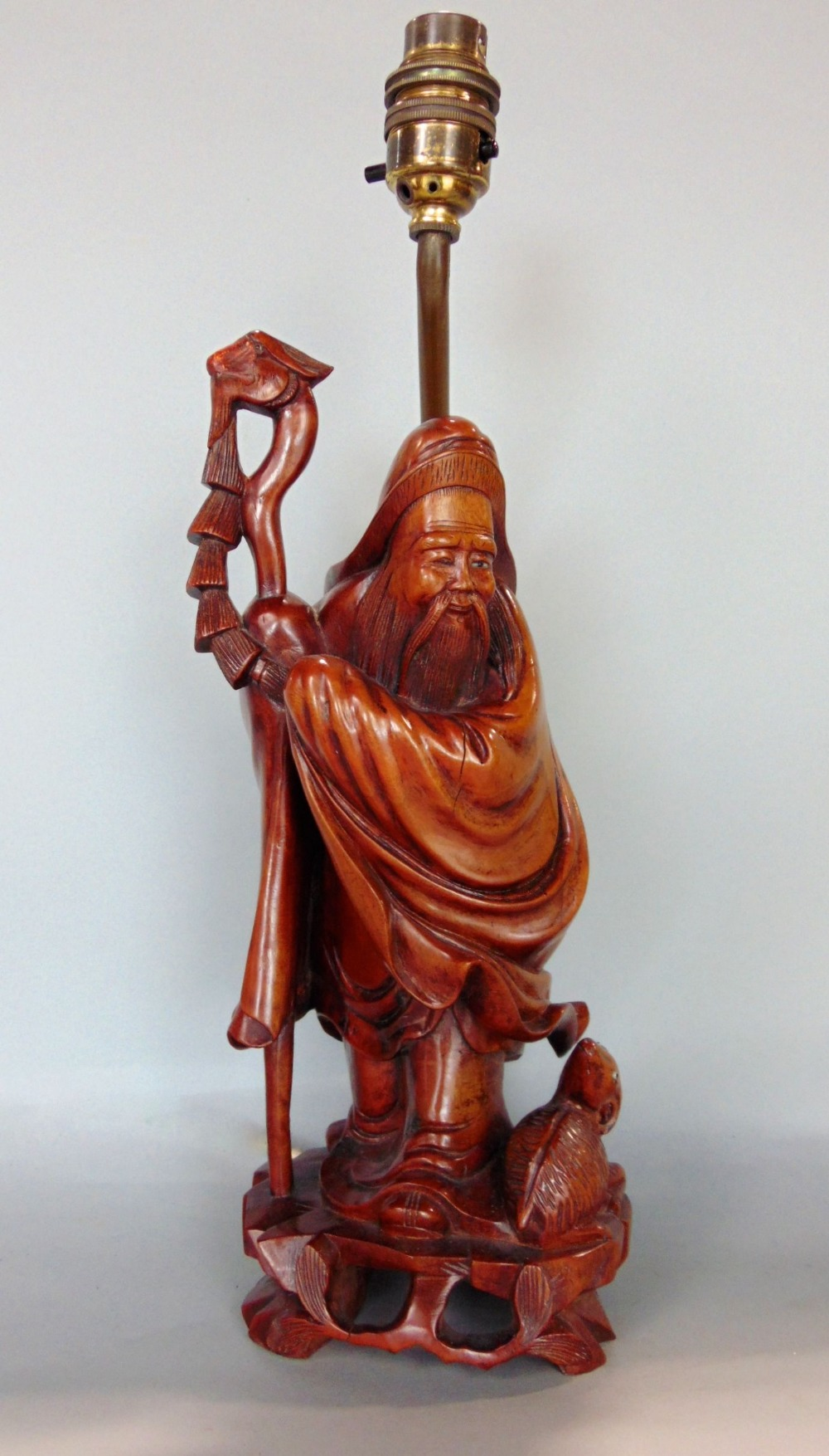 Lot 861 - Chinese hardwood carving of a standing sage holding a staff, 30 cm high, converted into a table