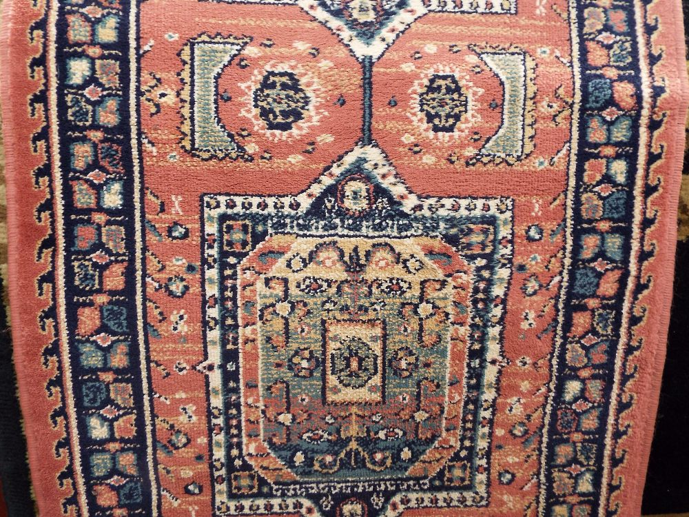 Lot 1443 - Axminster runner decorated with five blue medallions upon a pink ground, 300 x 65 cm