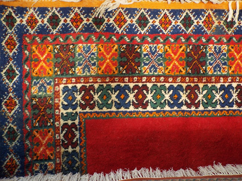 Lot 1414 - Kurdish type full pile carpet with a central blue medallion and borders upon a red ground, 340 x 240