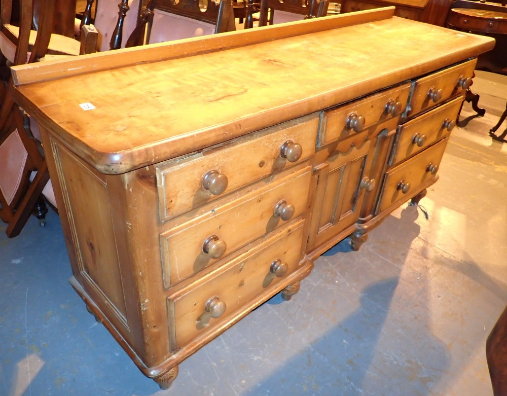 Lot 705 - Walnut buffet sideboard with seven drawers and a central cupboard on tulip feet 180 x 52 x 87 cm H