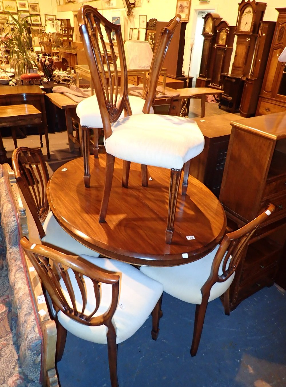 Lot 708 - Mahogany tilt top breakfast table on tripod base with six modern upholstered shield back dining