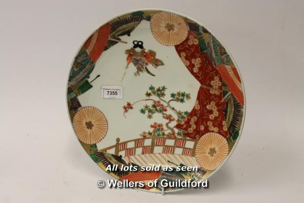 Lot 7355 - *A Japanese porcelain plate decorated with a figure, prunus and parasols, 31cm (lot subject to VAT)