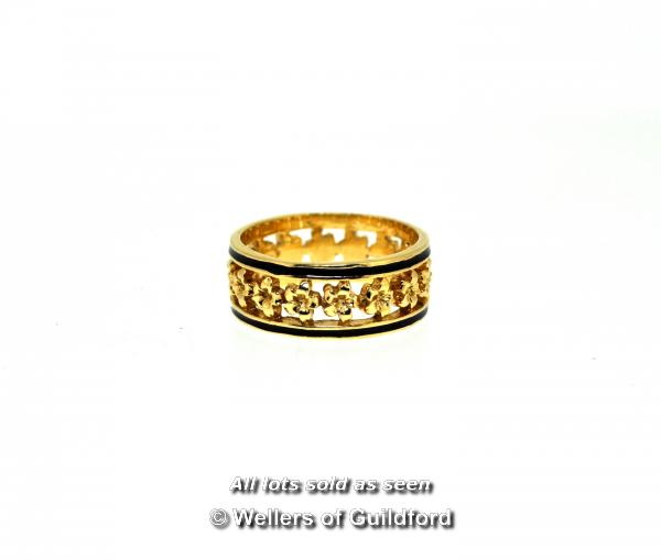 Lot 7006 - Ornate band ring, openwork band with a flower design and black enamel edges, in yellow metal stamped