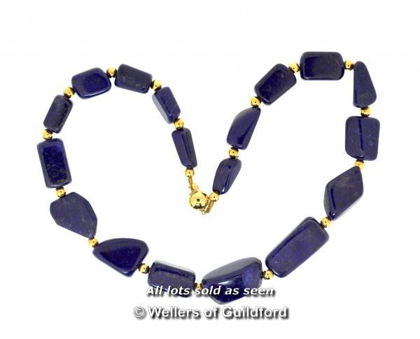 Lot 7026 - Lapis lazuli bead necklace, irregular shaped lapis lazuli beads with a yellow metal clasp stamped