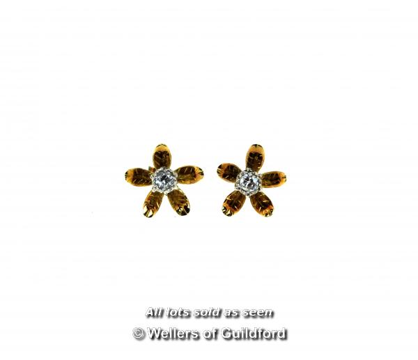 Lot 7011 - Single stone diamond ear studs, round cut diamonds mounted in a floral setting in yellow metal