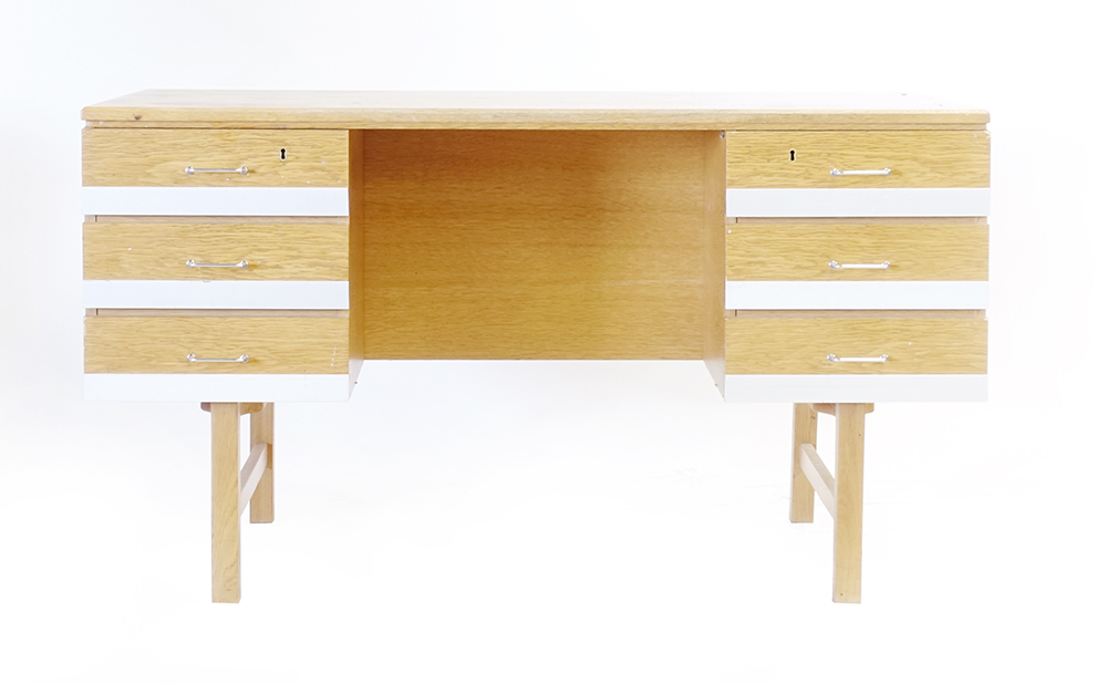 Lot 56 - A 1960/70's oak desk, the surface with bevelled edges over six drawers with aluminium front panels,