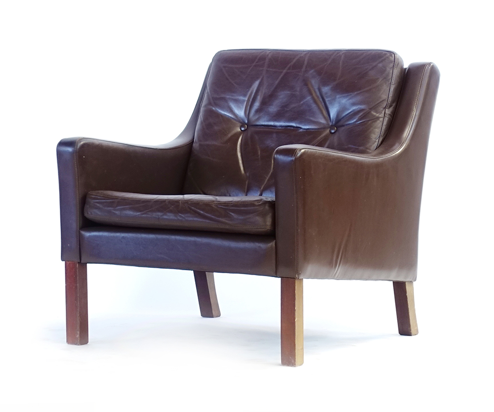 Lot 52 - A 1970's brown button upholstered lowback armchair on mahogany square feet CONDITION