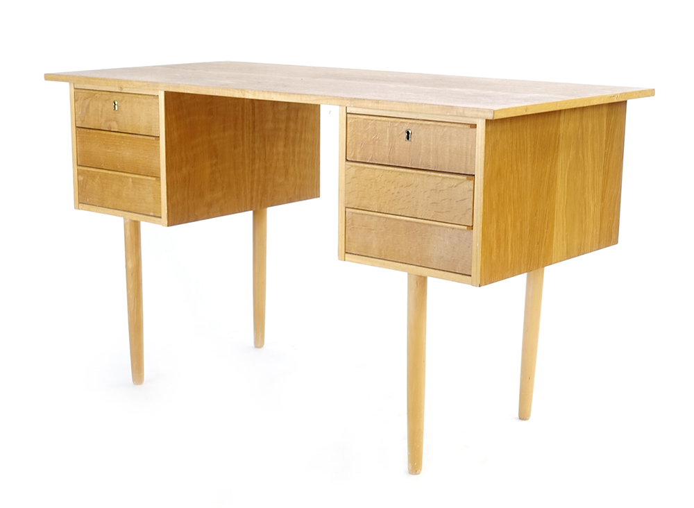 Lot 1 - A 1970's oak desk, the rectangular surface over six drawers on tapering beech legs,