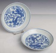 Paar Teller, China, Mitte 19. Jahrhundert, Blau-Weiß-Porzellan, mit Drachendekor. Die Us.m. blauer