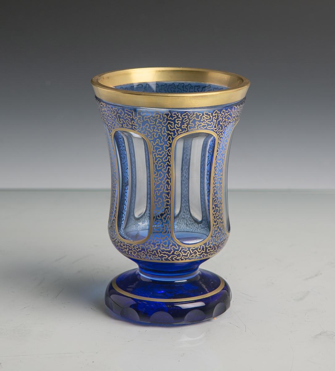 Lot 18 - Becherglas im Stil des Biedermeiers, farbloses Glas blau überfangen, Schliffdekor,Goldstaffage, H.