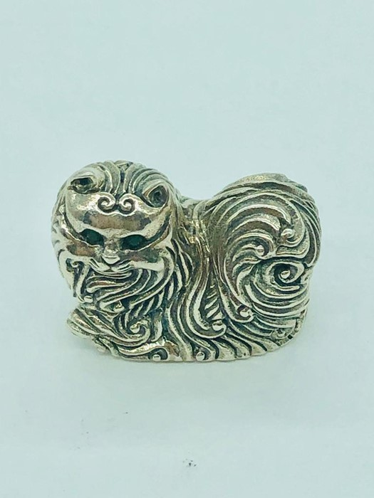 Lot 39 - A silver figure of a cat with emerald eyes