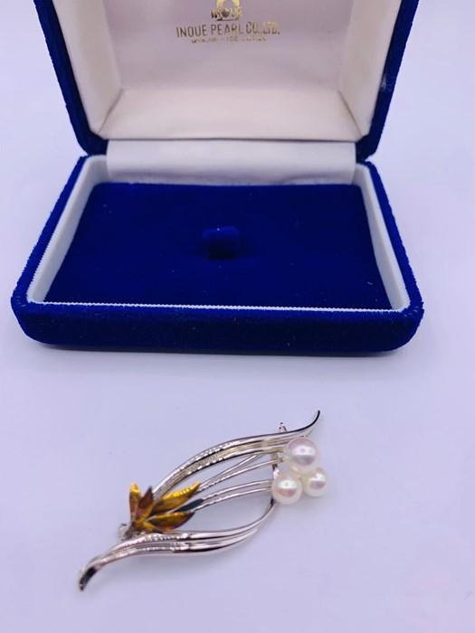 Lot 74 - A Japanese three stone Pearl brooch.