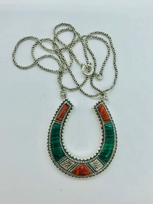 Lot 95 - A silver horseshoe necklace set with coral and malachite panels