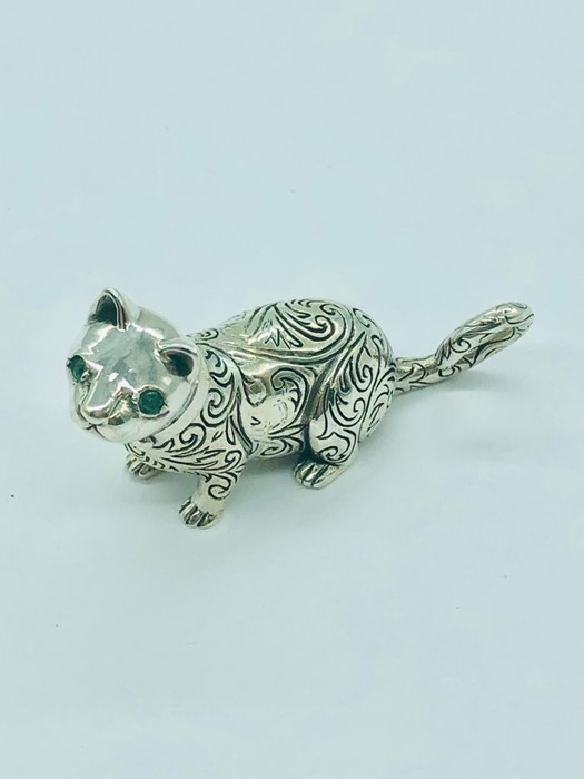 Lot 27 - A silver cat figure with emerald eyes