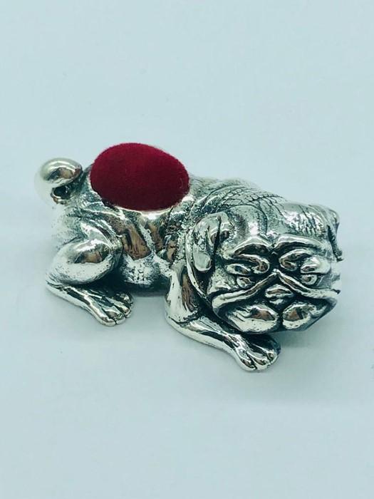 Lot 25 - A silver dog pincushion