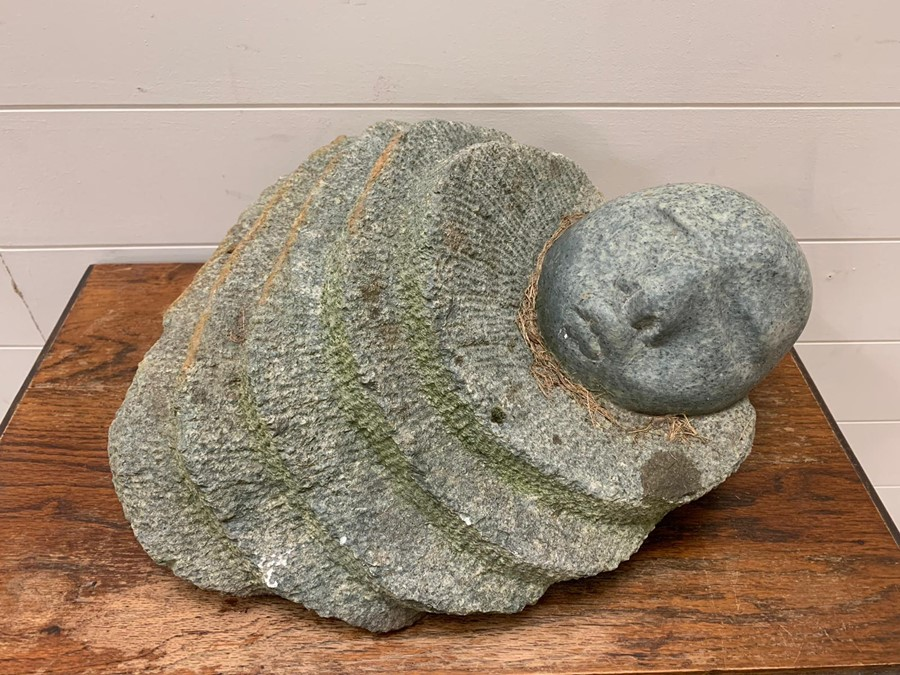 Lot 173 - A stone sculpture of a sleeping person.