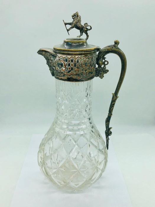 Lot 3 - A cut glass claret jug with silver plated fitments and lion with shield finial.