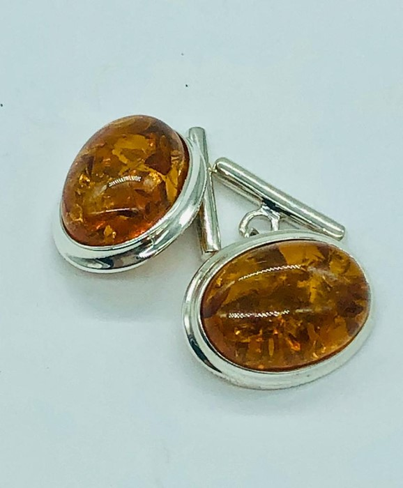 Lot 91 - A pair of silver and amber style cufflinks