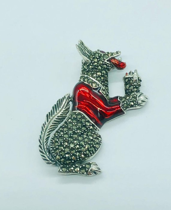 Lot 84 - A silver and enamel dog brooch with ruby eyes