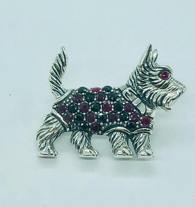 Lot 87 - A silver dog brooch with semi precious stone jacket and ruby eyes