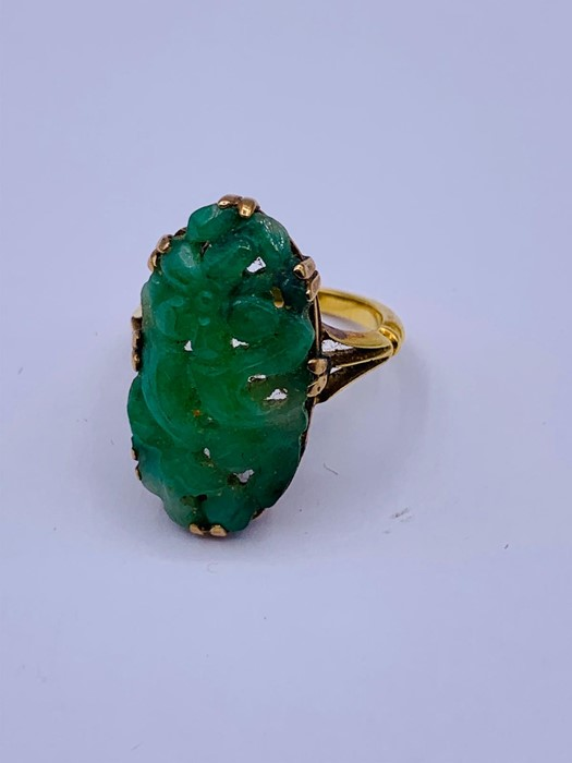 Lot 46 - A Chinese jade ring on gold band with indistinct hallmarks