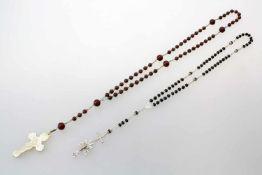 2 Rosenkränze - um 18501.) Braune Kugeln, daran Perlmuttkreuz. Länge: 50 cm. 2.) Schwarze Kugeln,