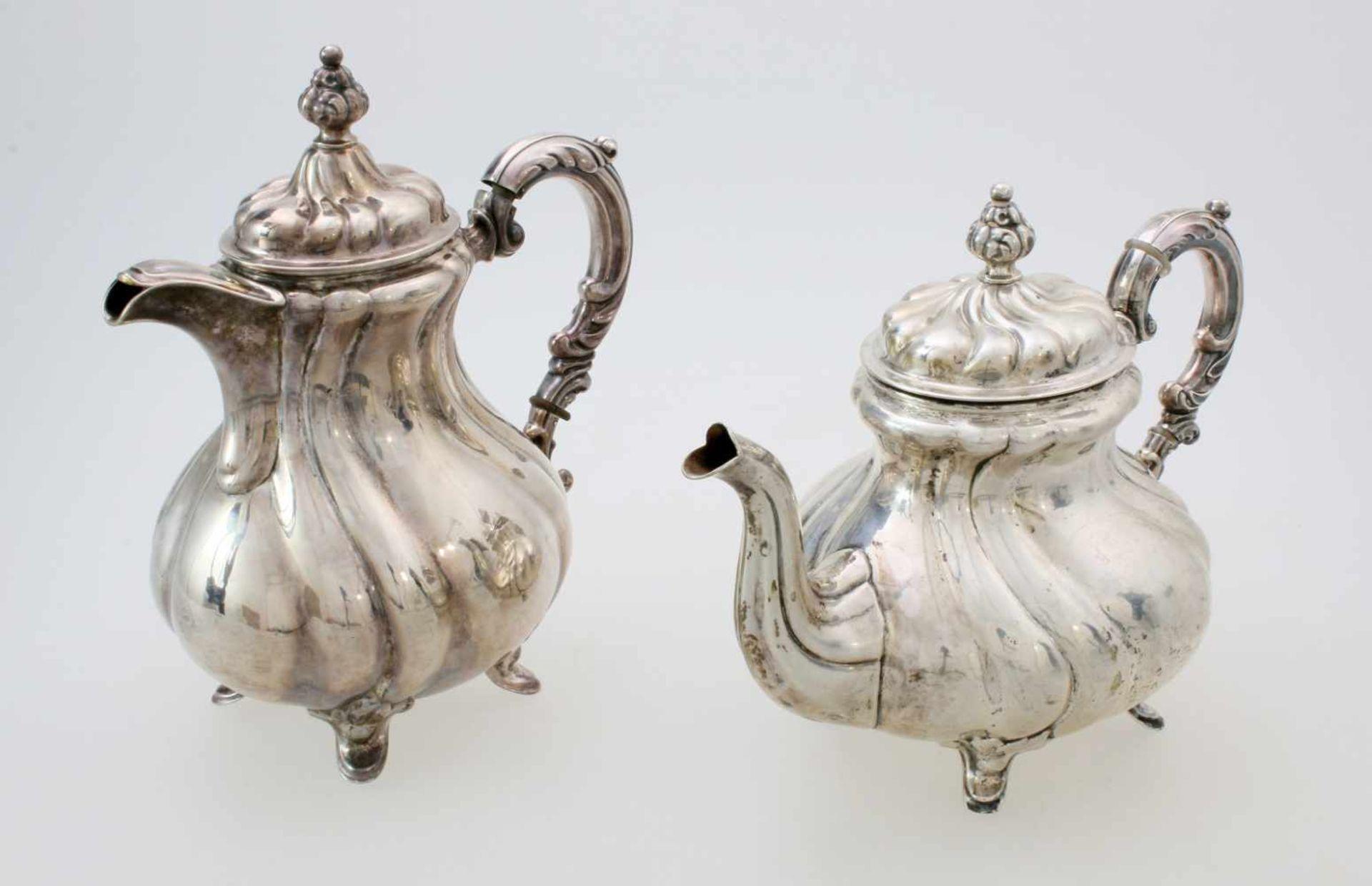 2 silberne Tee- und KaffeekannenBeide Kannen godronierter, bauchiger Korpus, Deckel en suite,