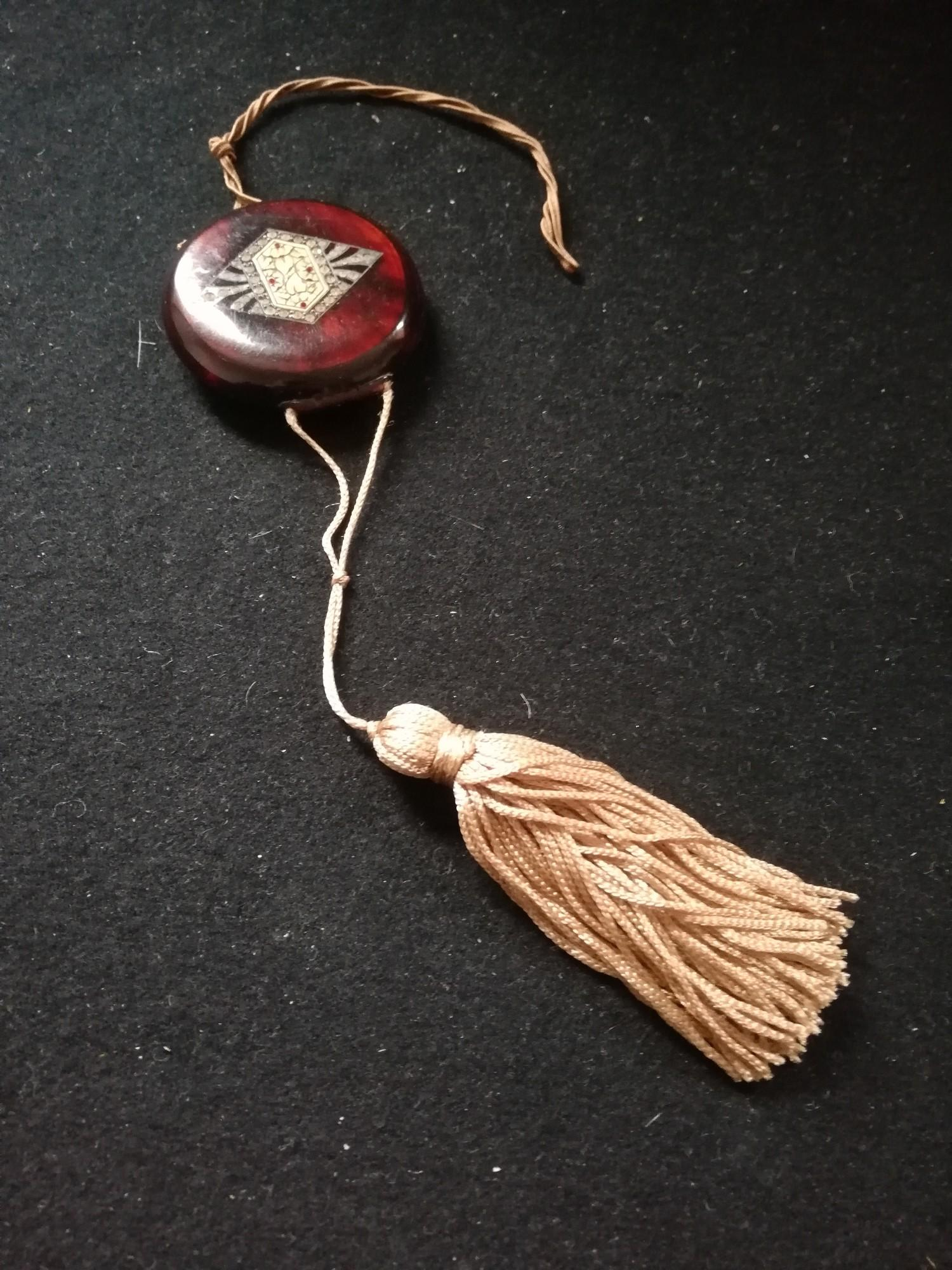 """Lot 126 - 1920's plastic compact with fabric tassel and chinese style design to front 2½""""diameter"""