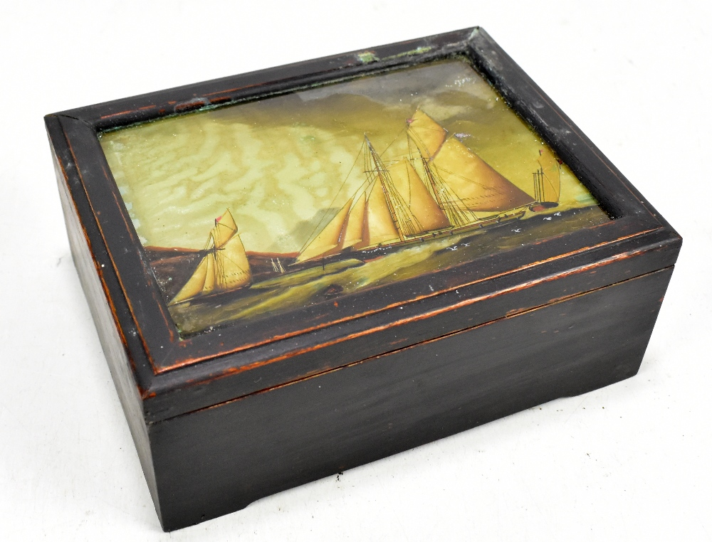Lot 39 - A mahogany box with glazed top with picture of boats.