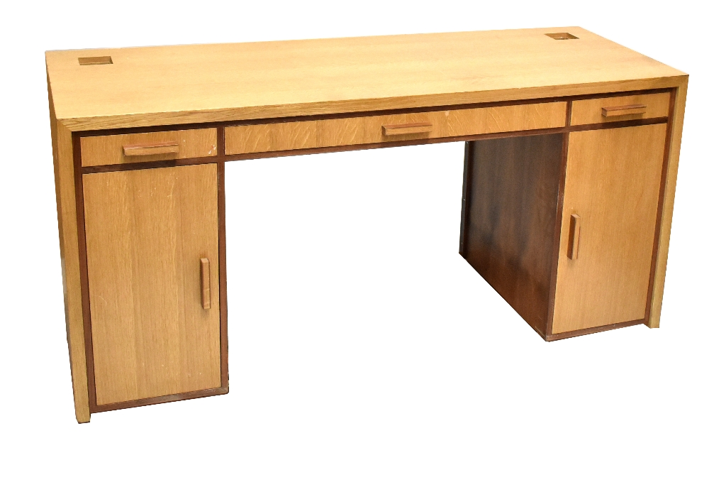 Lot 2561 - LINLEY FURNITURE; a light oak flat top kneeholedesk with three drawers above two panel cupboard