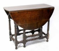 A late 17th/early 18th century oak gateleg table with pegged oval top with ruled edge,
