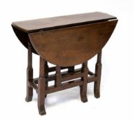 A George III oak dropleaf gateleg D-end table on turned and block legs with stretchers,