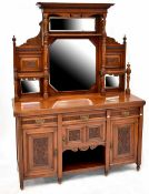 An Edwardian mahogany mirror-back sideboard, the central carved frieze above two central mirrors,