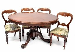 A Victorian mahogany oval tilt-top dining table on bulbous carved supports and tripod base and four