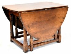 A reproduction oak gateleg supper table with oval top and on turned legs to block feet and